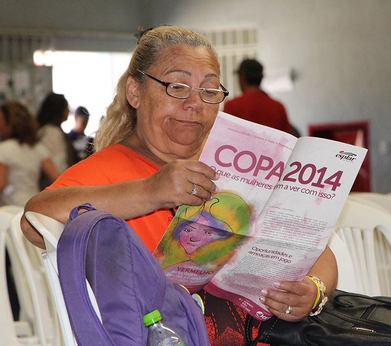 Participante do Encontro dos Atingidos em BH lê a publicação Copa 2014 - O que as mulheres tem a ver com isso?